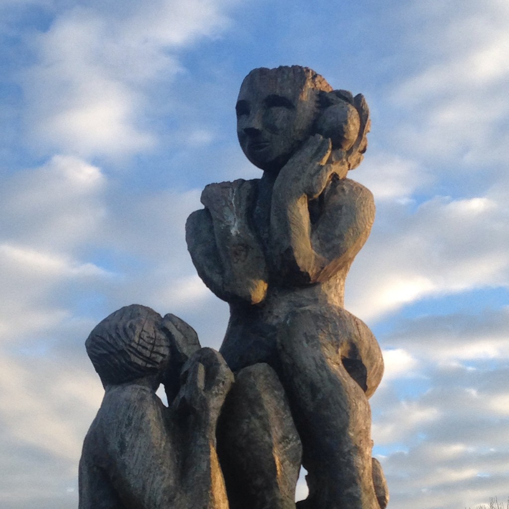 mother and baby statue against blue sky with cluds